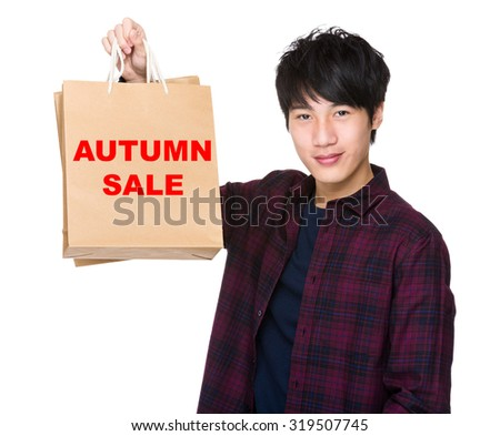 Asian Man hold with shopping bag and showing phrase of autumn sale