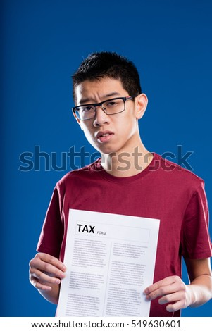 asian man holding a tax form looking very worried