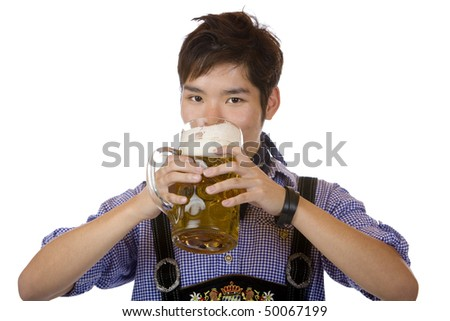 Asian man holding an Oktoberfest beer stein and drinks out of it. Isolated on white background. - stock photo