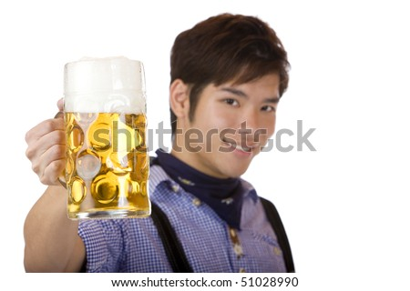 Asian man holding an Oktoberfest beer stein into camera and smiles. Focus on beer stein. Isolated on white. - stock photo