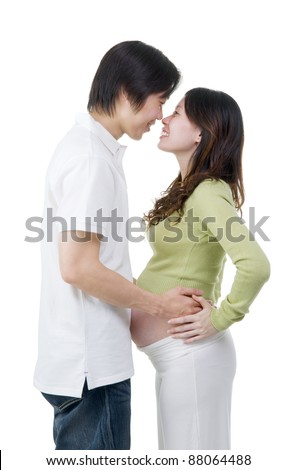 Asian man holding his pregnant wife's belly isolated on white background.
