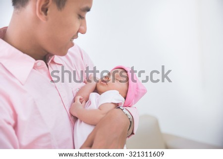 Asian man holding his sleeping baby girl, close up - stock photo