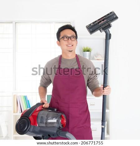 Asian man holding vacuum. House husband doing house chores, house interior. - stock photo