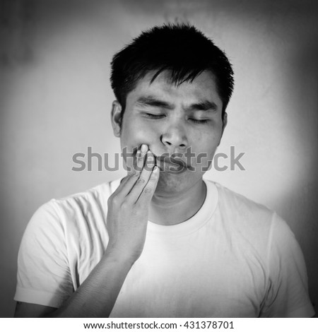 Asian man in a white t-shirt has a toothache /healthy concept  - stock photo