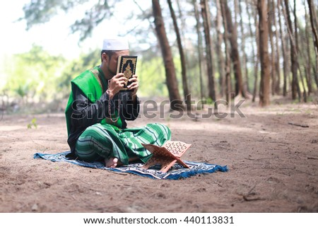 Asian man in arabic clothes reading Quran at outdoor - stock photo