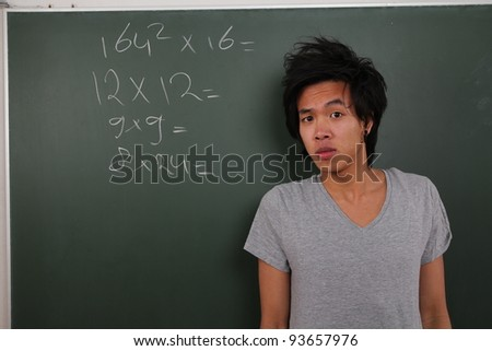 Asian man in front of a schoolbord