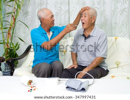 Asian man is checking his father's body temperature with a digital thermometer. - stock photo