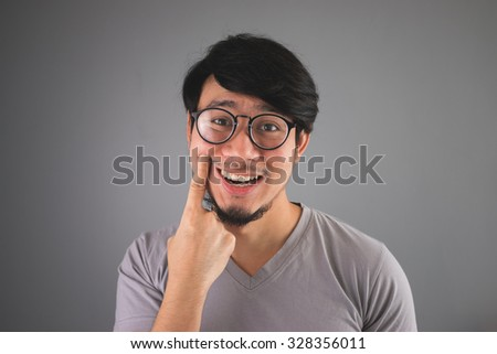 Asian man is faking his smile. - stock photo