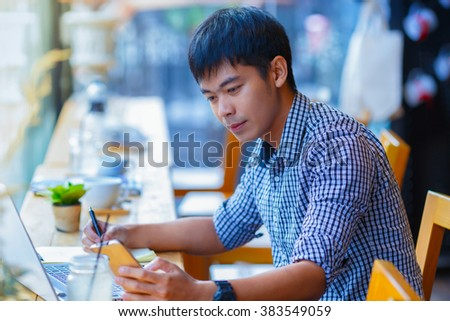 asian man looking to a smart phone in coffee shop - stock photo