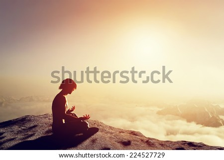 Asian man meditates in yoga position in high mountains above clouds at sunset. Unique concept of meditation, spirituality, balance, harmony in life. - stock photo