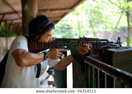 Asian man posting in ready position to shoot an AK-47 rifle. - stock photo