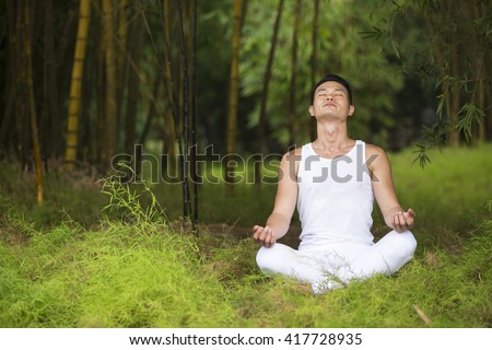 Asian man practicing yoga in a garden. healthy lifestyle and relaxation