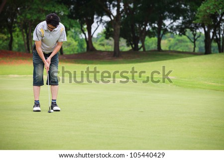 Asian man putting on golf course - stock photo