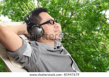 Asian man relax in nature & enjoying good music - stock photo