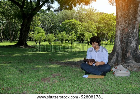 asian man resting and reading a book under a tree in a green park