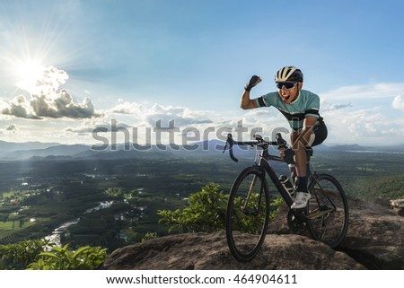 Asian man riding a bike on a cliff .