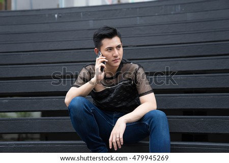 Asian man sits at outdoor with smart phone.