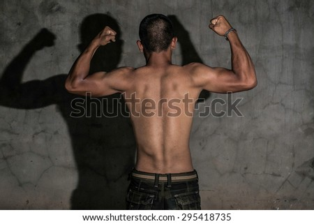 Asian Man Standing behind the show, the muscles on the gray. - stock photo