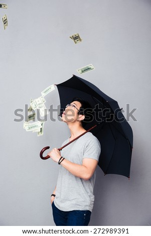 Asian man standing in the rain of money over gray background - stock photo