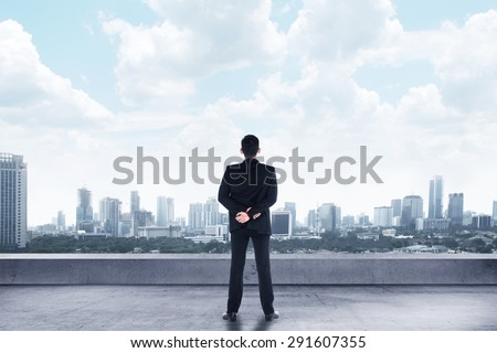 Asian man standing looking the city from rooftop - stock photo