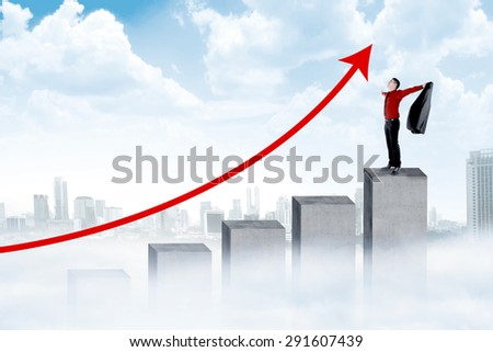 Asian man standing on the chart celebrate his success - stock photo