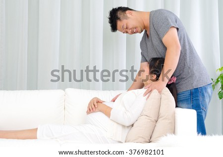 Asian man talking with his pregnant wife