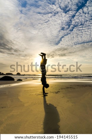 Asian man turn upside-down and standing by hands or hand stand, silhouetted against sunlight - stock photo