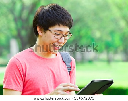 Asian man using tablet in the park - stock photo