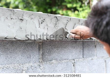 Asian man using trowel with wet concrete wall in construction site - stock photo