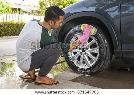 Asian man washing car's alloy wheels on a car wash. Cleaning concept.