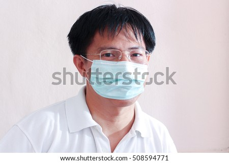Asian man wearing glasses is sick with mask, asian man wearing medical mask, young thai man wearing protective mask
