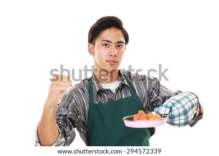 Asian man wearing kitchen apron  - stock photo