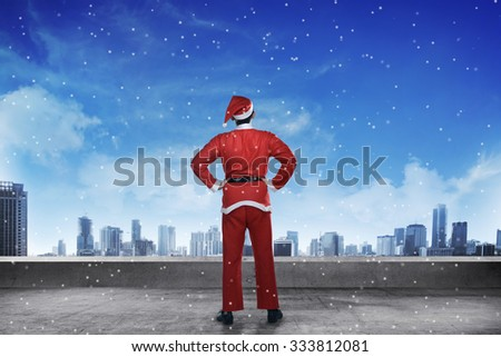 Asian man wearing santa claus costume standing on the building rooftop looking the city - stock photo