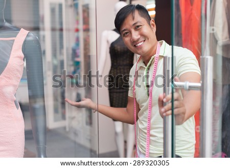 Asian man welcome tailor shop fashion clothes dress designer small business owner - stock photo
