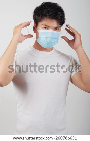 Asian man with blue dust mask - stock photo