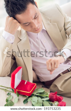 Asian man with bouquet and wedding ring waiting for his girlfriend - stock photo