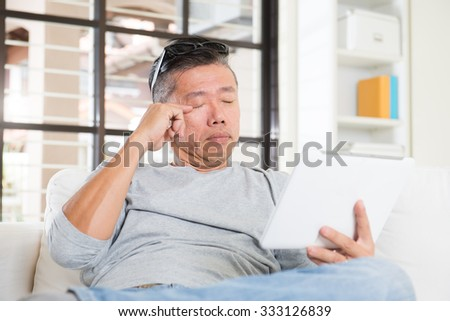asian man with eyes problem after long hours of using computer tablet - stock photo