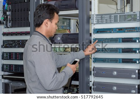 Asian man with mobile phone in hand checking server status in data center