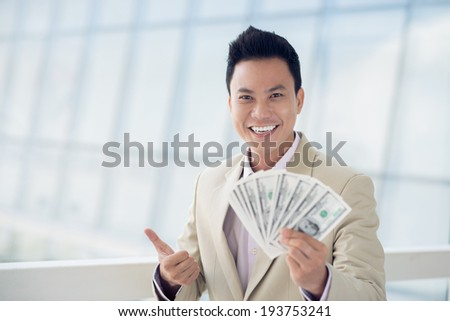 Asian man with money showing thumbs up - stock photo