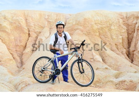 Asian man with mountain bike on rocks. Sport and active life concept. - stock photo