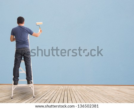 Asian MAn With Paintbrush  And Blue Blank Wall - stock photo