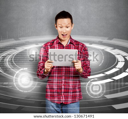 Asian man with touch pad in his hands got good news - stock photo