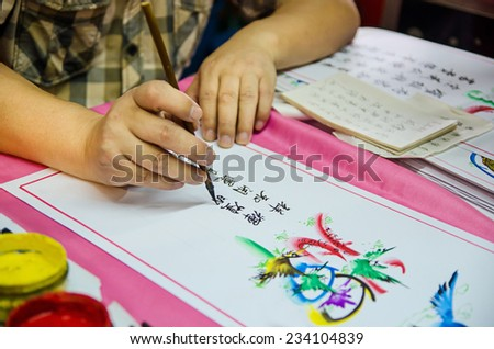 Asian Man writing Chinese Calligraphy on a paper.