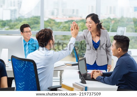 Asian manager giving high five - stock photo