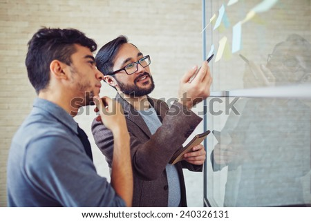 Asian manager pointing at reminder while talking to colleague in office - stock photo