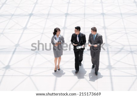 Asian managers walking and discussing documents, view from above - stock photo