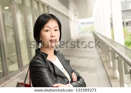 Asian mature woman at street, closeup portrait. - stock photo
