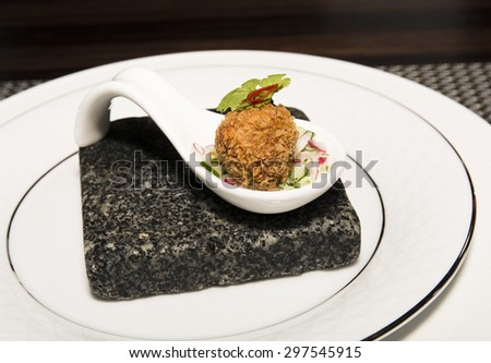 Asian meatballs, garnished with herb and red pepper in white chinese spoons served on black rock dish.