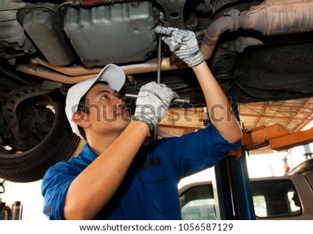 Asian mechanic is looking under the car to repair the engine,japanese mechanic portrait style