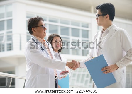 Asian medical team of doctors shaking hands inside hospital building - stock photo